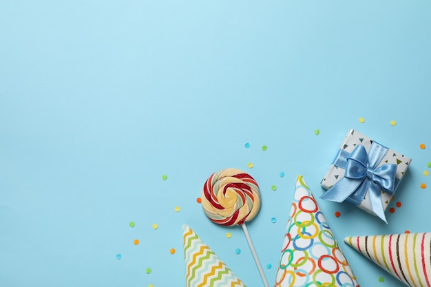 Birthday hats, gift box and lollipop on blue background, space for text