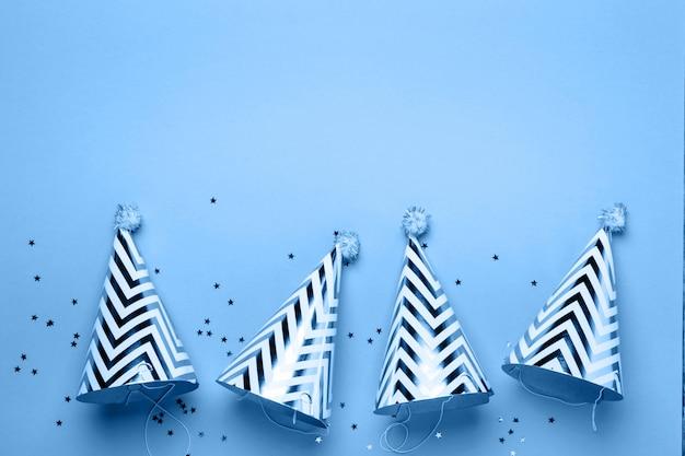 誕生日休日パーティーコンセプト。ストライプコーン帽子と紙吹雪。青の色合い
