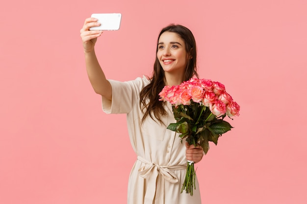 Birthday, holidays, romance concept. charming alluring young caucasian woman receive delivery, got gift flowers, taking selfie on smartphone with beautiful bouquet, standing happy pink wall