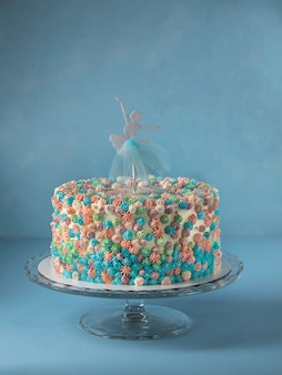 Birthday layer cake decorated with ballerina cake topper on sky blue background