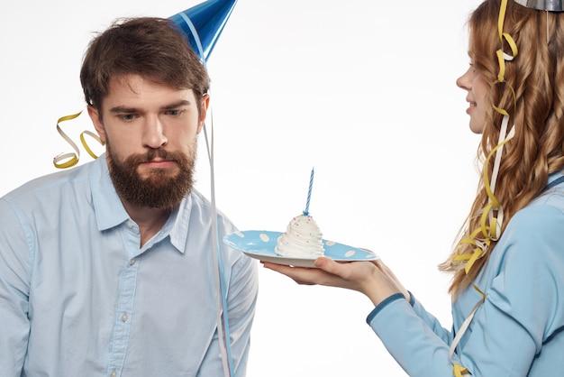 カップケーキとパーティーハット、白い壁のキャンドルで誕生日男女