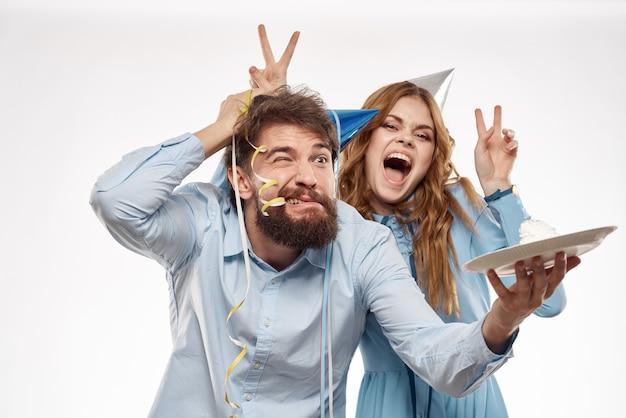 誕生日の男女とカップケーキとパーティーハットのキャンドル