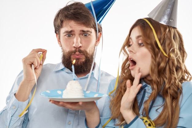 Именинник и женщина с кексом и свечой в праздничной шляпе