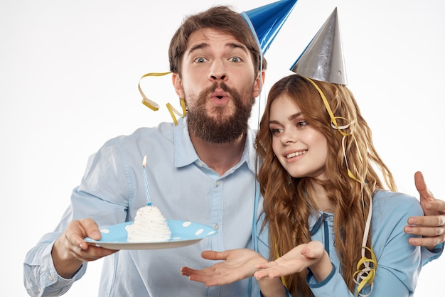 Birthday man and woman with a cupcake and a candle in a party hat, white wall