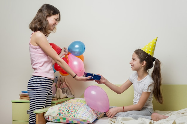 Birthday morning. older sister giving surprise gift to her cute little sister. children at home in bed