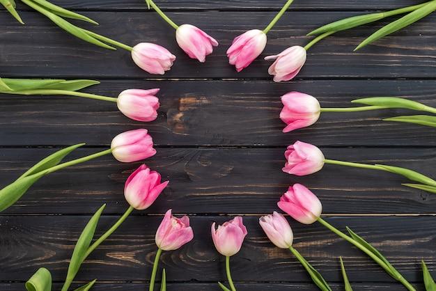木製の背景の上にピンクのチューリップの花の誕生日や結婚式のモックアップ。