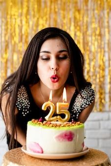 생일 파티. 생일 케이크에 촛불을 불고 검은 파티 드레스에 매력적인 백인 여자