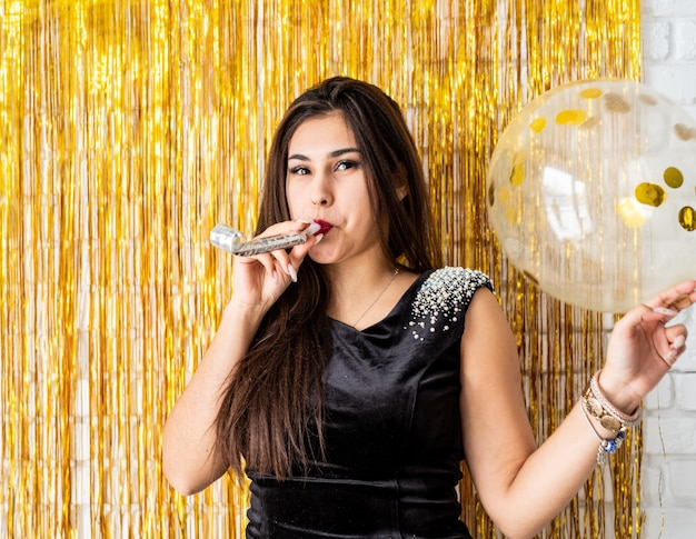 Birthday party. beautiful brunette woman in black party dress celebrating her birthday blowing the noise maker