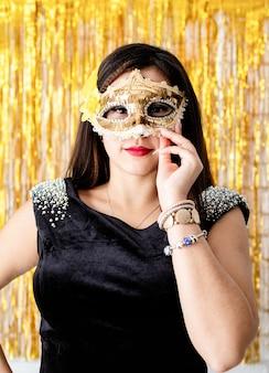 생일 파티. 빛나는 황금 무도회 마스크를 쓰고 검은 파티 드레스에 아름 다운 갈색 머리 여자