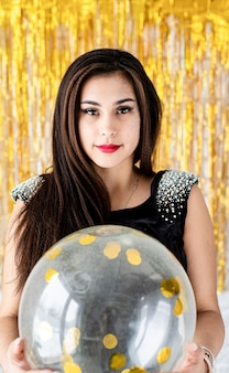 Birthday party. beautiful smiling brunette woman in black party dress celebrating her birthday holding balloon