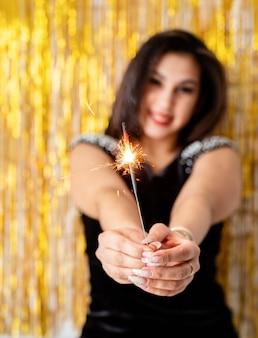 День рождения. красивая молодая женщина, держащая бенгальский огонь и воздушный шар на золотом фоне