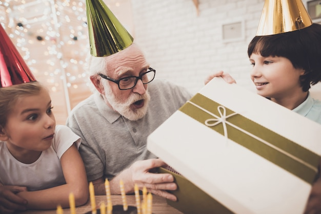 Birthday party boy gives box to surprised grandpa.