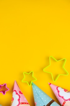 Birthday party caps and stars on yellow