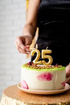 생일 파티. 생일 케이크에 검은 파티 드레스 조명 촛불에 백인 여자