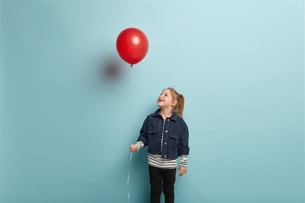Birthday party and childhood concept. horizontal shot of glad little child with ginger hair, looks happily upwards on red air balloon, wears fashionable clothes, stands over blue wall