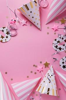 誕生日パーティーのコンセプト。ピンクの背景にパーティーハット、マスク、バースデーキャンドル。コピースペースのあるトップダウンビュー