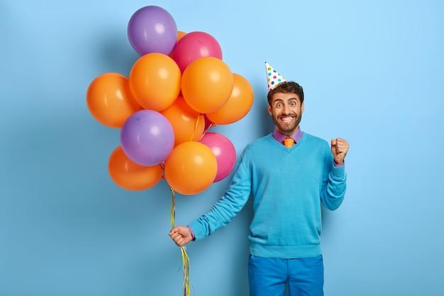 Концепция вечеринки по случаю дня рождения. позитивный мужчина сжимает кулаки от счастья
