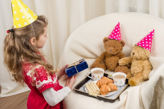 Birthday party, girl kid in festive hat playing with teddy bears