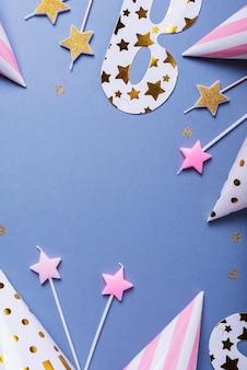 パーティーハット、マスク、キャンドル、テキスト用のコピースペースを備えたトップダウンビューの誕生日パーティーの招待状