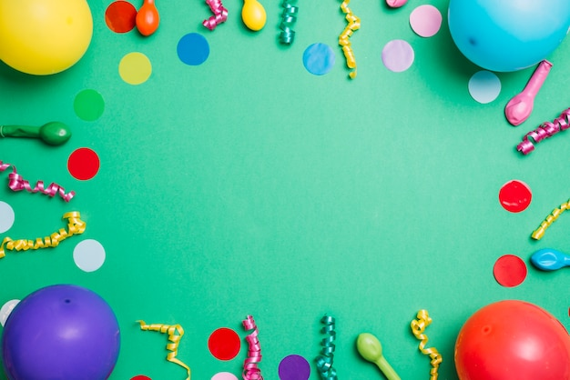 Birthday party items on green background with colorful confetti