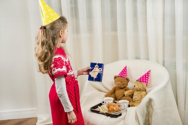 Вечеринка по случаю дня рождения, ребенок в праздничной шляпе, играющей с плюшевыми мишками.