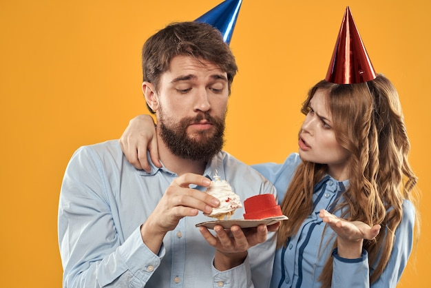 誕生日パーティーの男性と女性の楽しみ黄色の背景キャップ休日