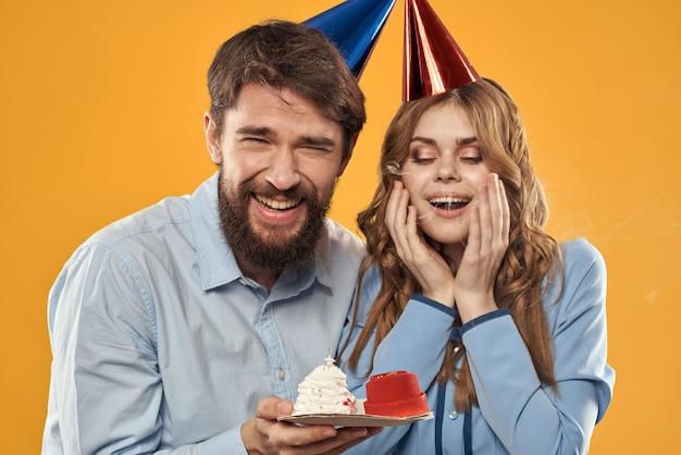 誕生日パーティーの男性と女性の楽しい黄色の背景