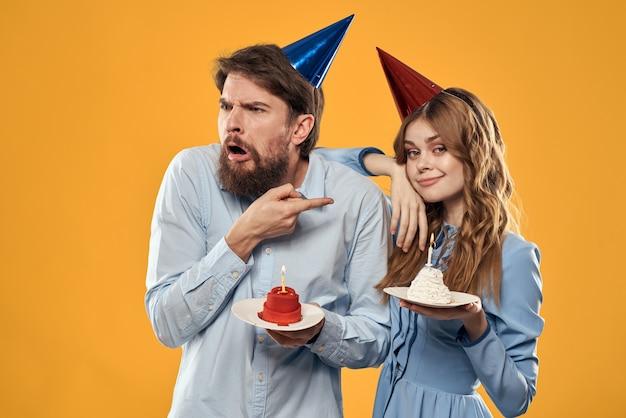 誕生日パーティーの男性と女性の楽しい黄色のキャップの休日