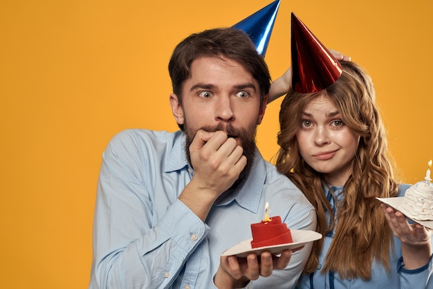 誕生日パーティーの男性と女性の楽しい黄色の壁のキャップの休日。