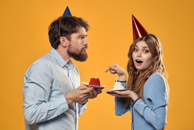 誕生日パーティーの男性と女性の楽しい黄色の壁のキャップの休日