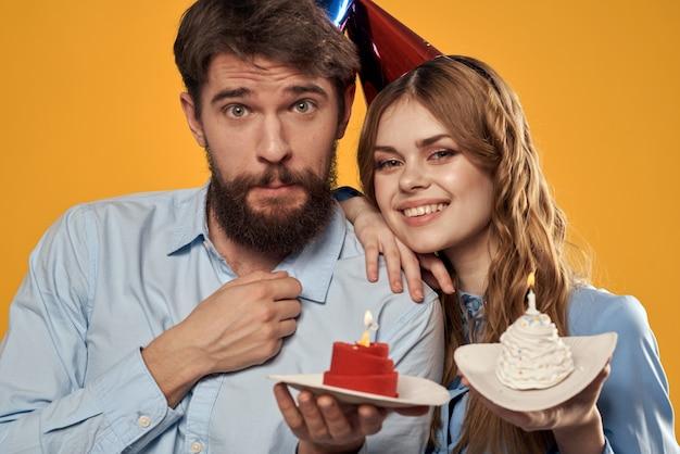 黄色の背景のトリミングされたビューにケーキとキャップの誕生日パーティーの男性と女性