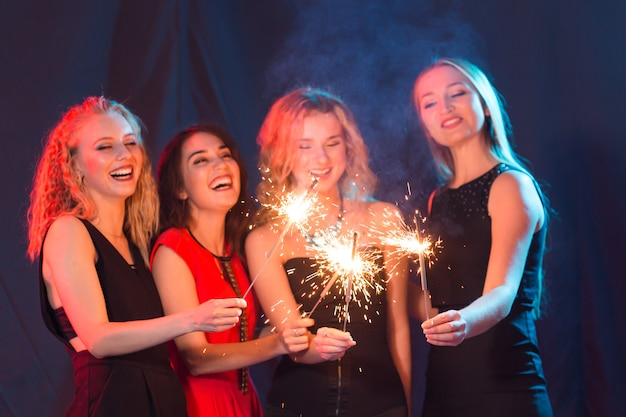 誕生日パーティー、新年と休日のコンセプト-線香花火の開催を祝う女性の友人のグループ。