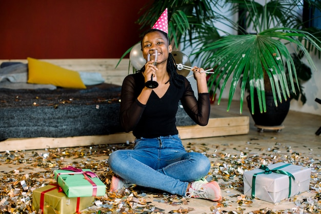 Birthday party, new year carnival. young african smiling woman celebrating brightful event, . sparkling confetti, having fun, dancing and drinking champagne