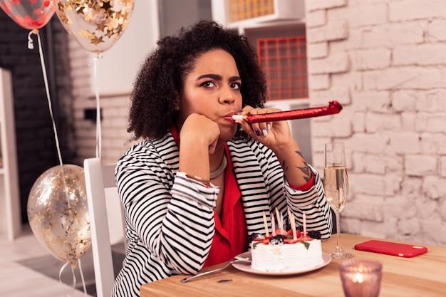 생일 파티. 손님을 기다리는 동안 축제 테이블에 앉아 좋은 사려 깊은 여자