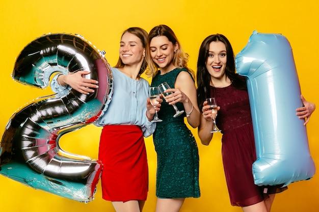 생일 파티. 기념일을 축하하는 최신 유행의 옷을 입은 세 매력적인 여성