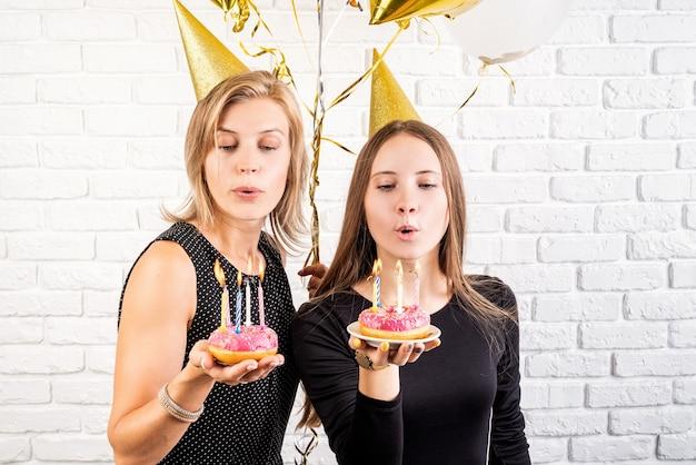 생일 파티. 흰색 벽돌 벽 배경 위에 촛불 도넛을 들고 생일을 축하하는 생일 모자에 두 웃는 젊은 여성 또는 자매