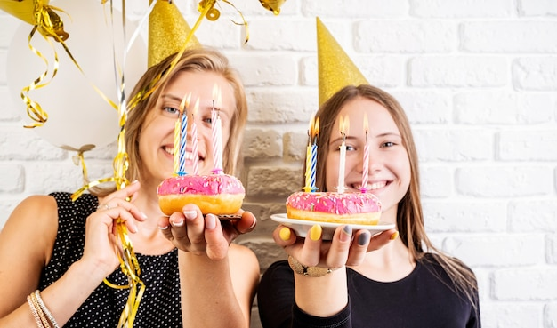 Birthday party. two smiling young women or sisters in birthday hats celebrating birthday holding donuts with candles over white brick wall background