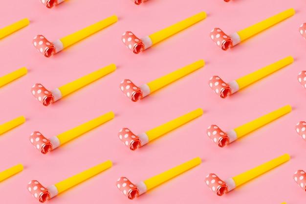 생일 파티는 분홍색 배경, 파티 송풍기 뿔, 최소한의 파티 개념으로 다채로운 축하 패턴에 휘파람.
