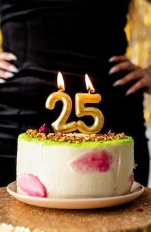 생일 파티. 그녀의 스물 다섯 번째 생일을 축하하는 생일 케이크를 먹을 준비가 검은 파티 드레스에 여자