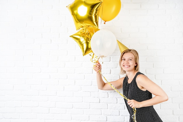 Birthday party. young blond smiling woman wearing birthday hat holding golden balloons celebrating birthday with copy space