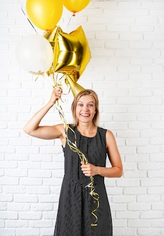 Birthday party. young blond smiling woman wearing birthday hat holding golden balloons celebrating birthday
