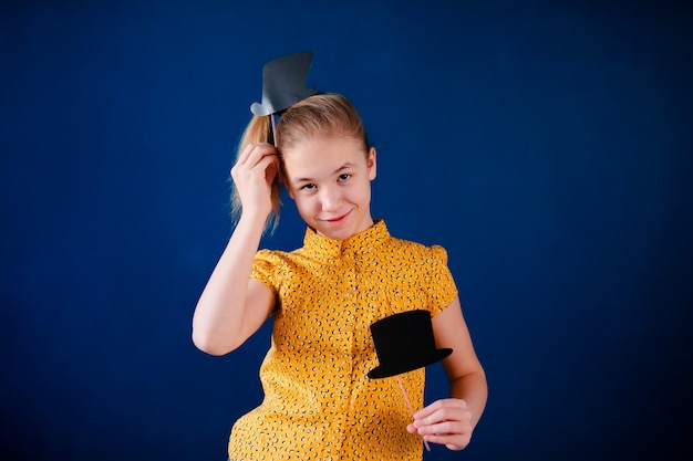 Birthday party and young girl in hats and props on blue wall