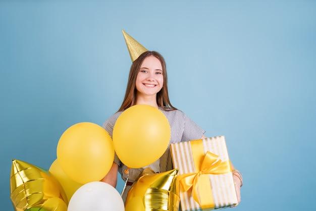 생일 파티. 풍선 및 복사 공간 파란색 배경 위에 생일 파티를 축하하는 큰 선물 상자를 들고 생일 모자에 젊은 여자