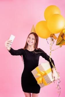 생일 파티. 핑크 배경 위에 셀카를 복용 생일 파티를 축하하는 풍선과 큰 선물 상자를 들고 생일 모자에 젊은 여자