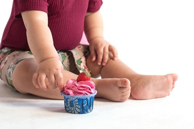 소녀의 첫 번째 생일을 축하하는 생일 핑크 케이크 망가진 스폰지 케이크 깨진 마시맬로 아기 손과 지연