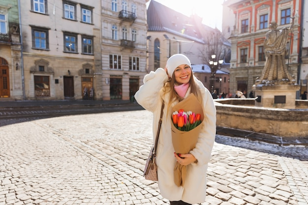 Birthday present for a beautiful girl in a white fur coat old town square cold sunny day