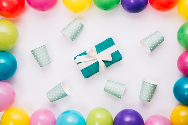 Il presente di compleanno circondato con la tazza eliminabile dentro i palloni rasenta il fondo bianco