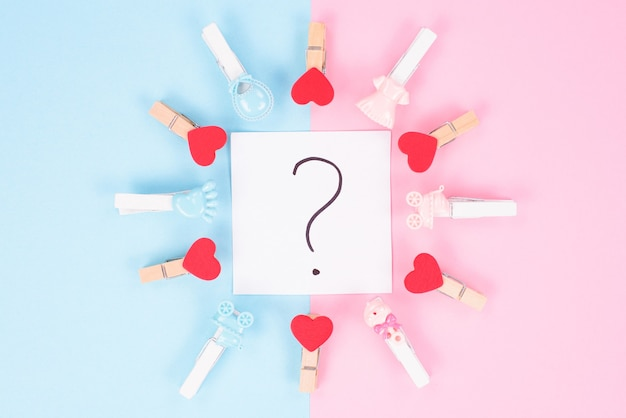 Birthday studio soft color composition concept. photo of question mark in the middle between divided background and isolated clothes pings pegs