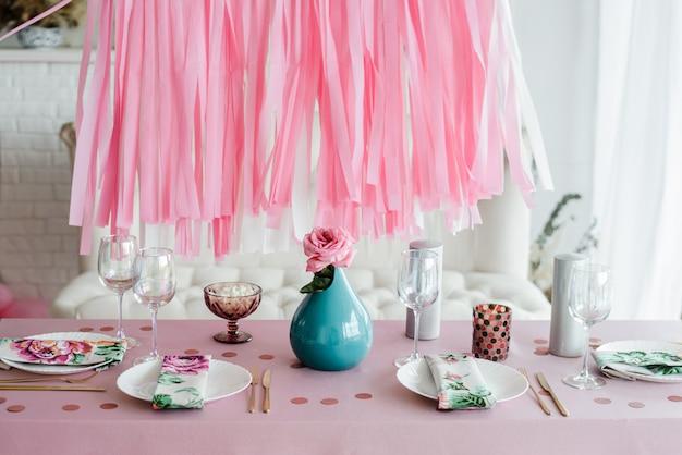 Сервировка стола дня рождения в розовом и цвета с розой в вазе. стримеры гирлянды фон. детский душ, девушка украшение вечеринки.