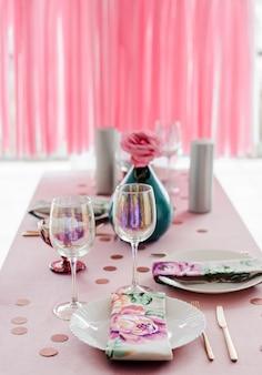 Сервировка стола дня рождения в розовом и цвета с розой в вазе. стримеры гирлянды фон. детский душ или девичник.